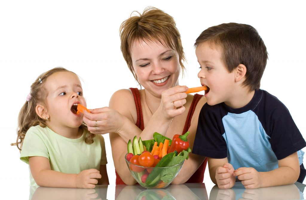 Woman feeding kids with fresh vegetables - the joy of eating healthy food